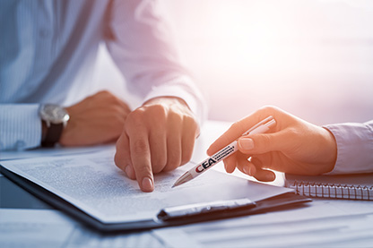 hand of an insurance agent holding a pen pointing at a CEA policy on a clipboard
