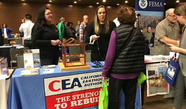 Melissa Crittenden and Chelsea Talbert, CEA staff, talking to a San Francisco resident about the importance of earthquake insurance and house retrofitting.